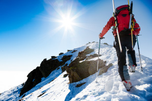 Mountaineer walking up along a snowy ridge with the skis in the