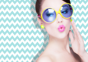 Attractive surprised young woman wearing sunglasses on zig zag b